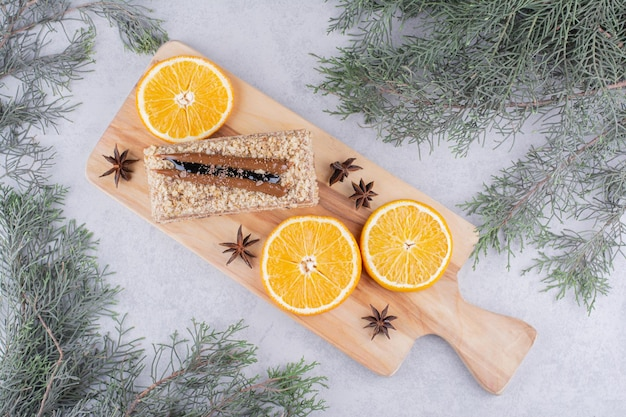 Bolo caseiro com cravo e rodelas de laranja na placa de madeira.