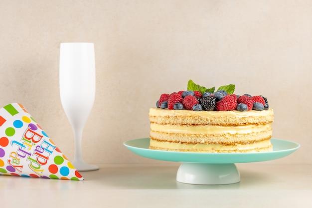 Bolo caseiro com frutas frescas e chapéu de aniversário na brilhante.