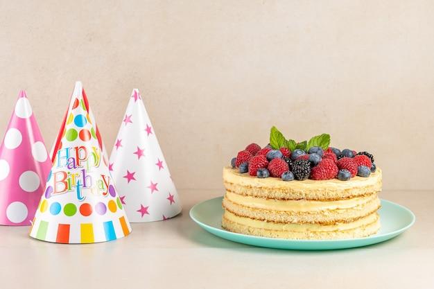 Bolo caseiro com frutas frescas e chapéu de aniversário no fundo brilhante.