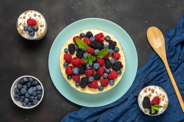 Bolo caseiro com frutas frescas e sobremesas doces em fundo escuro.