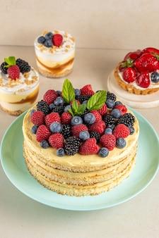 Bolo caseiro com frutas frescas e sobremesas doces na mesa.