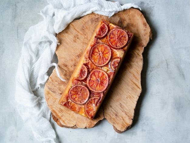 Bolo caseiro com laranjas de sangue em uma placa de madeira e fundo cinza claro