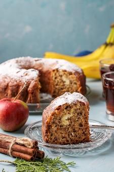 Bolo caseiro com maçãs, bananas e canela, polvilhado com açúcar sobre uma superfície azul clara, um pedaço de bolo em primeiro plano