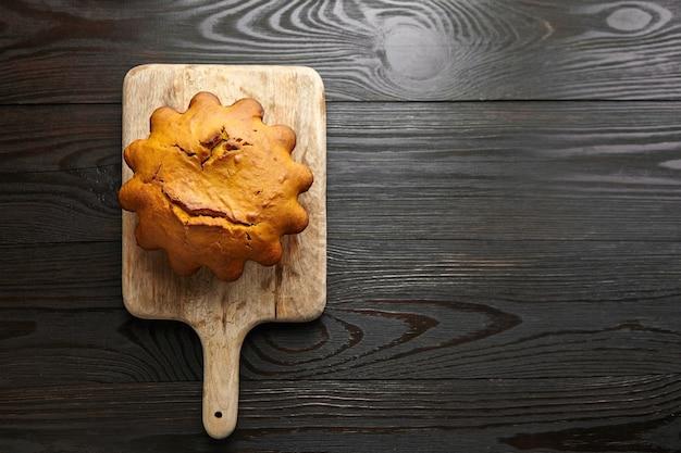 Bolo caseiro de abóbora de outono em uma tábua de madeira em fundo escuro, vista superior, copie o espaço