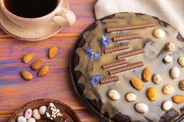 Bolo caseiro de brownie de chocolate com creme de caramelo e amêndoas com café em uma superfície de madeira colorida e tecido de linho