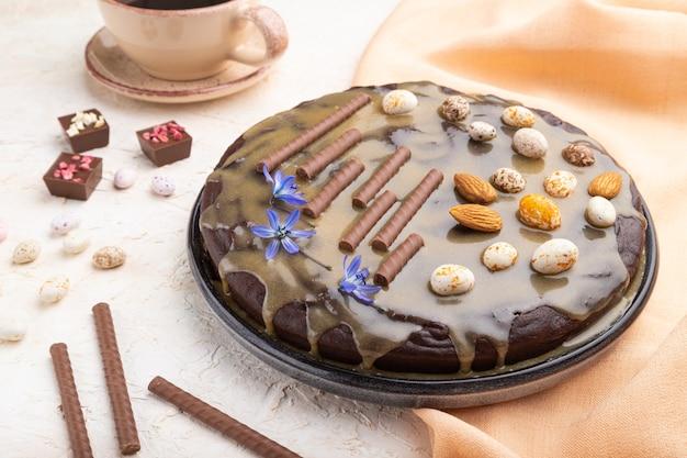 Bolo caseiro de brownie de chocolate com creme de caramelo e amêndoas com xícara de café em uma superfície de concreto branco e tecido laranja