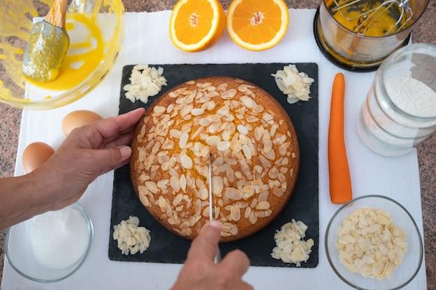 Bolo caseiro de cenoura recém-assado. mãos do chef com faca. ingredientes e utensílios de cozinha que foram usados para fazer isso