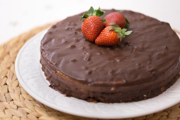 Bolo caseiro de chocolate amargo com cacau e morangos orgânicos frescos por cima servido no prato branco