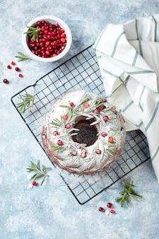 Bolo caseiro de chocolate amargo feito em casa, decorado com açúcar de confeiteiro e cranberries frescas em uma grade de metal com fundo azul claro