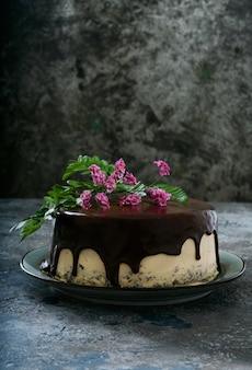 Bolo caseiro de chocolate com camadas de creme de manteiga de amendoim decorado com flores na parte superior sobre uma mesa escura e rústica. vista lateral.