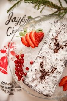 Bolo caseiro de chocolate de natal polvilhado com açúcar de confeiteiro com groselha e morangos