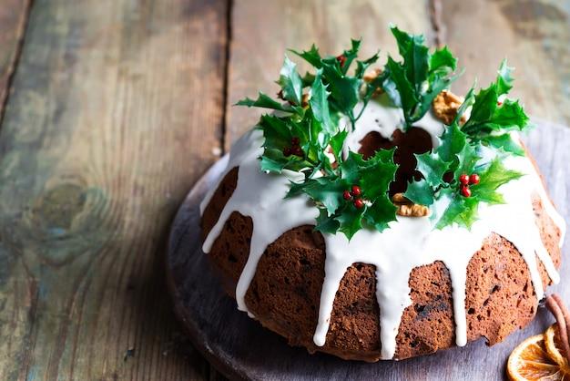 Bolo caseiro de chocolate escuro homebaked de natal decorado com glacê branco e holly berry ramos em um rústico de madeira velho