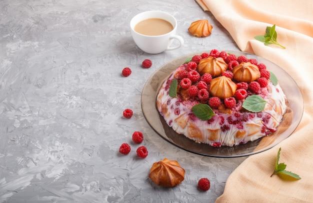 Bolo caseiro de geléia com leite, biscoitos e framboesa com xícara de café e têxtil laranja, vista lateral.