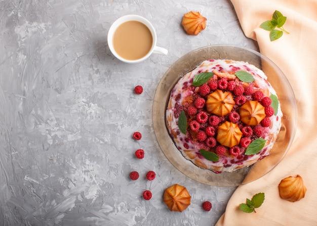 Bolo caseiro de geléia com leite, biscoitos e framboesa com xícara de café e têxtil laranja, vista superior.