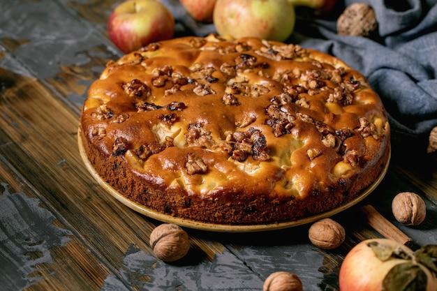 Bolo caseiro de maçã e nozes charlotte no prato com maçãs frescas de jardinagem, canela e nozes ao redor na mesa de prancha de madeira escura. cozimento caseiro outonal.