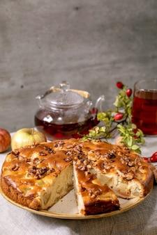 Bolo caseiro de maçã e nozes charlotte no prato com maçãs frescas para jardinagem, nozes, chá de rosa mosqueta na toalha de mesa de linho cinza. cozimento aconchegante outonal.