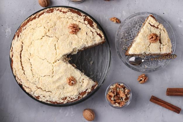 Bolo caseiro de migalhas com nozes e canela em um prato sobre uma mesa de concreto cinza e corte um pedaço de bolo, vista superior, closeup