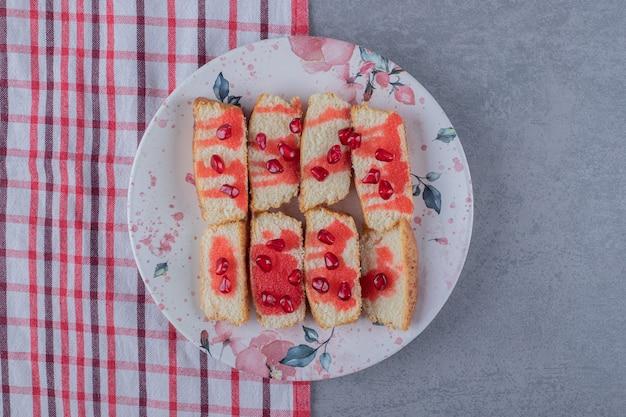 Bolo caseiro de toranja em prato branco com sementes de romã