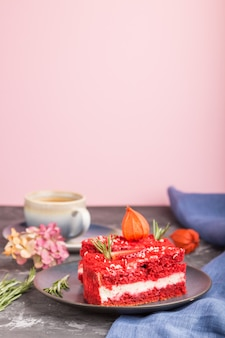 Bolo caseiro de veludo vermelho com creme de leite e morango com xícara de café em uma parede preta e rosa. vista lateral, foco seletivo, cópia espaço.