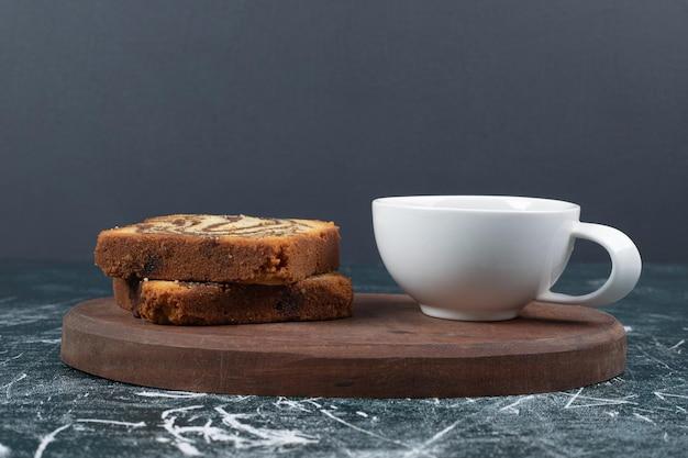 Bolo caseiro de zebra e xícara de chá na placa de madeira.