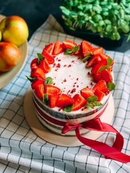 Bolo caseiro delicioso e suculento decorado com morangos com verduras nas costas