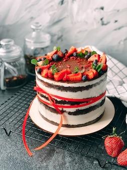 Bolo caseiro delicioso e suculento decorado com morangos vivos e frutas vermelhas