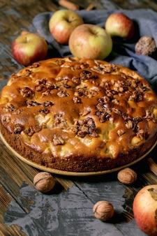 Bolo caseiro doce de maçã e nozes charlotte no prato com maçãs frescas de jardinagem, canela e nozes ao redor na mesa de prancha de madeira escura. cozimento caseiro outonal.