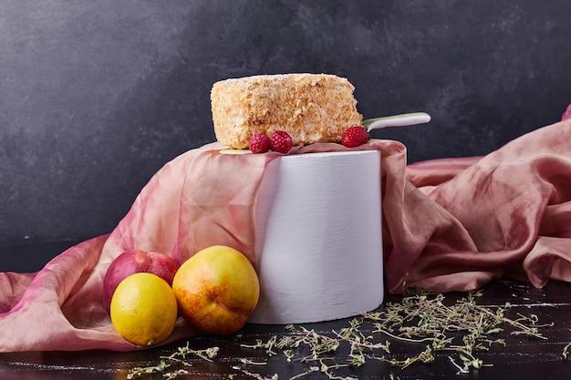 Bolo caseiro em fundo escuro com frutas, ameixas e toalha de mesa rosa.