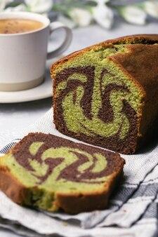Bolo caseiro fatiado de pistache de chocolate em mármore em forma de pão sobre uma toalha com uma xícara de café