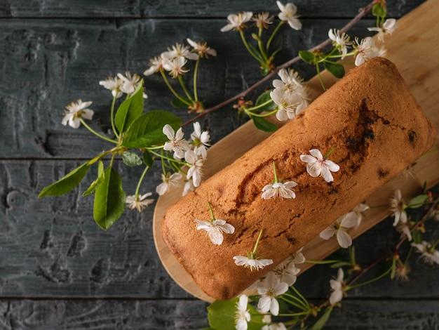 Bolo caseiro fresco decorado com flores de cerejeira na mesa escura