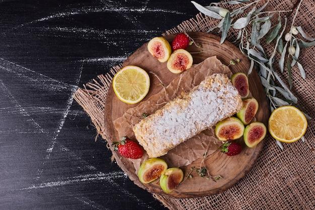 Bolo caseiro rodeado por várias frutas em uma bandeja de madeira redonda.