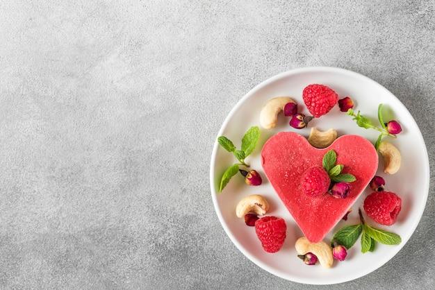 Bolo caseiro vegetariano cru com framboesas frescas, hortelã e caju. sobremesa de dia dos namorados. vista superior com espaço de cópia