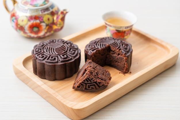 Bolo chinês de lua cheia com sabor de chocolate amargo em prato de madeira