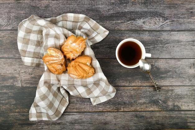 Bolo choux com café em um de madeira. em uma cesta em uma toalha quadriculada. . chique com queijo cottage. bolos de creme pequeno na tigela de vime na madeira