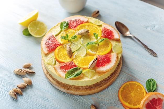 Bolo cítrico cru com toranja, laranja, lima e limão com nozes e hortelã