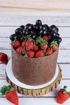 Bolo coberto com chocolate, decorado com uvas e morangos, sobre uma mesa de madeira branca (foto vertical).