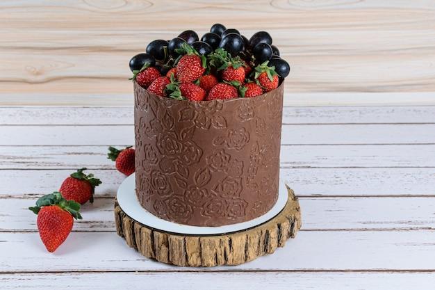 Bolo coberto com chocolate, decorado com uvas e morangos, sobre uma mesa de madeira branca.
