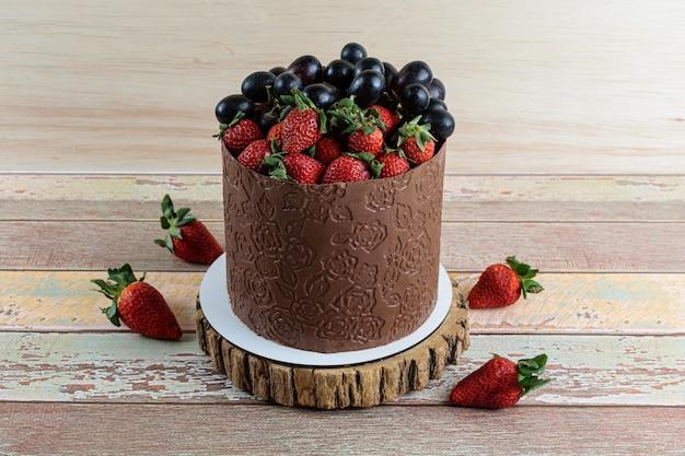 Bolo coberto com chocolate, decorado com uvas e morangos, sobre uma mesa de madeira.