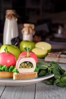 Bolo coberto com esmalte rosa sobremesa europeia luxuosa que parece uma maçã com folha verde