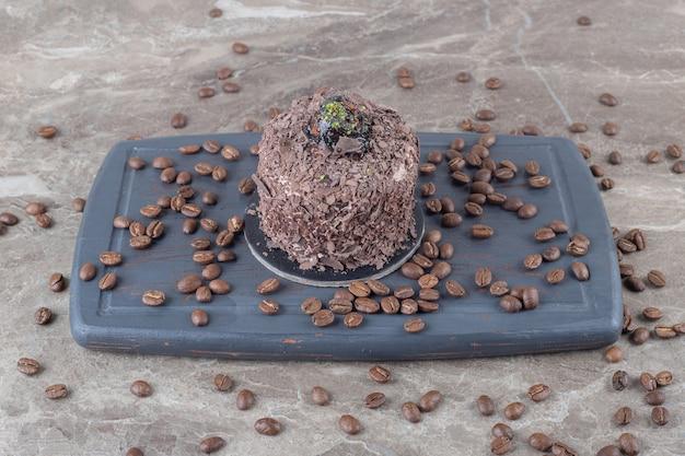 Bolo coberto de chocolate e grãos de café em um tabuleiro marinho sobre superfície de mármore