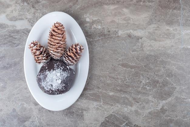 Bolo coberto de chocolate e três pinhas em uma travessa na superfície de mármore