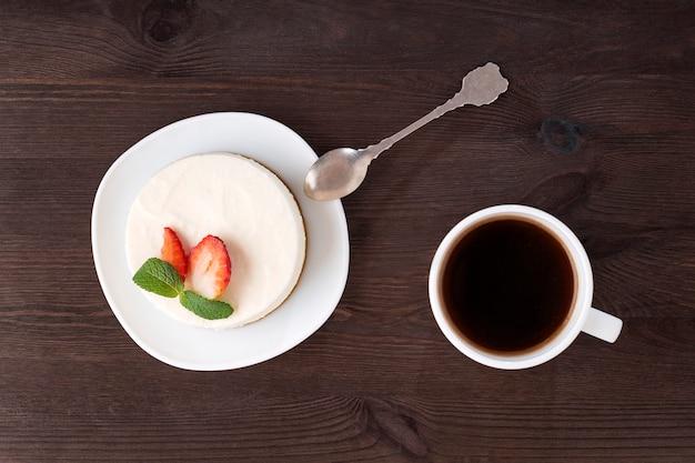 Bolo, colher de sobremesa e xícara de café em superfície de madeira