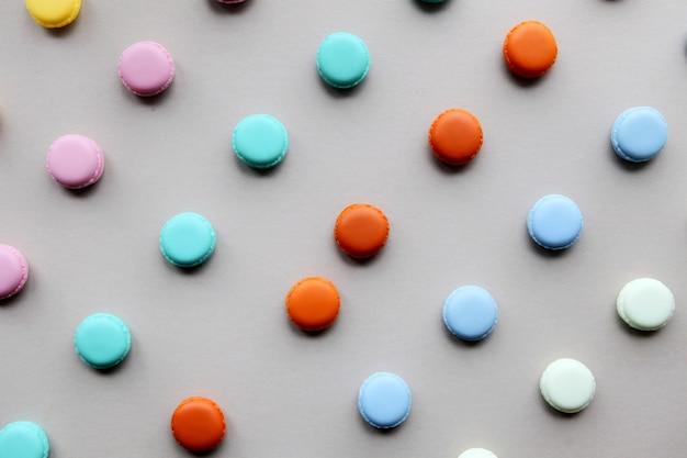 Bolo colorido de macarons naturais, vista superior plana leiga, macaroon doce em fundo cinza. padrão de macaroons de conceitos mínimos acima, plano de fundo de alimentos