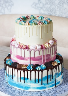Bolo colorido de três camadas com manchas coloridas de chocolate em uma luz. imagem para um menu ou catálogo de confeitaria com espaço para copiar