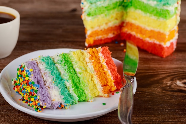 Bolo colorido do arco-íris de aniversário com uma xícara de café e uma faca.