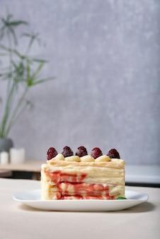 Bolo com calda de frutas silvestres decorada com framboesas. pedaço de bolo de frutas.