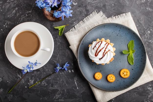Bolo com chantilly creme de ovo em uma placa de cerâmica azul com kumquat e folhas de hortelã