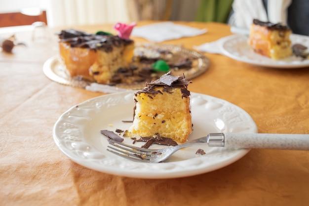 Bolo com chocolate em prato branco em cima da mesa