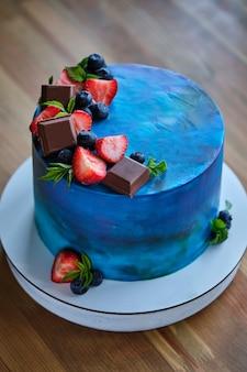 Bolo com chocolate em uma mesa de madeira. bolo decorado com frutas frescas e folhas de framboesa. sobremesa de aniversário. sobremesa deliciosa e linda.