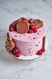 Bolo com chocolate sobre um fundo de mármore. bolo decorado com chocolate e frutas frescas. sobremesa de casamento e aniversário. sobremesa deliciosa e linda.